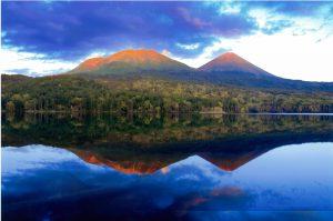 風のないオンネトーの夕景、夕陽が照らす雌阿寒岳と阿寒富士の神々しい姿を澄み切った湖面が映し出している。